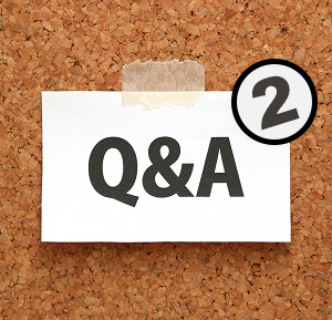 Q&A or Questions and Answers on a piece of white paper on a brown cork board.