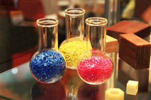 Colored polymer granules in glass flasks in factory.