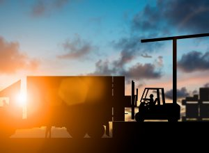 Silhouette Forklift truck lifting cargo container on a truck in the warehouse during sunset.