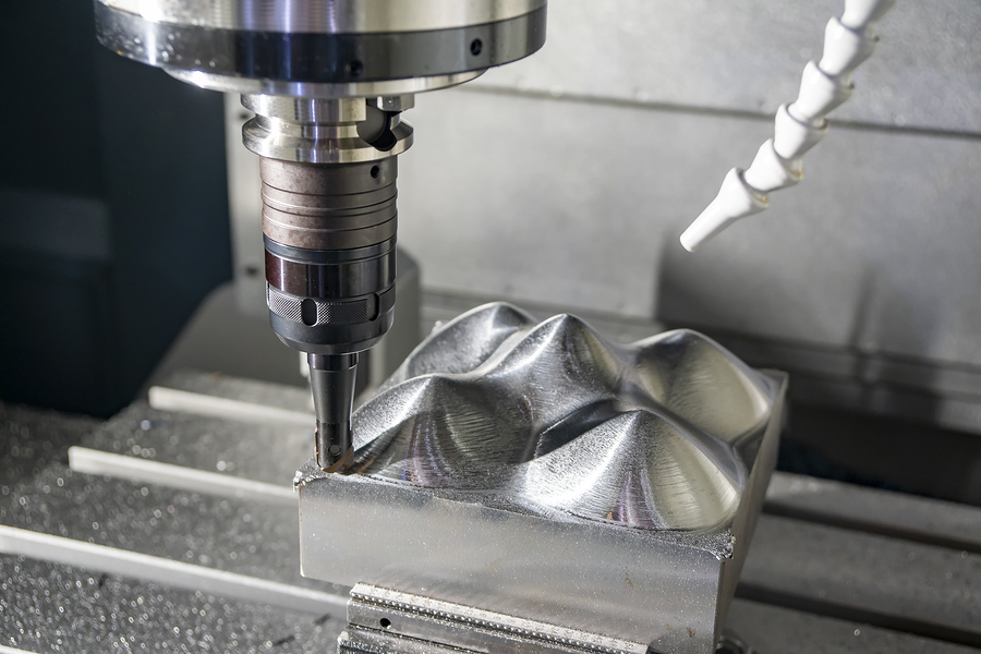 A milling machine modifying an injection mold by trimming steel from the tool.