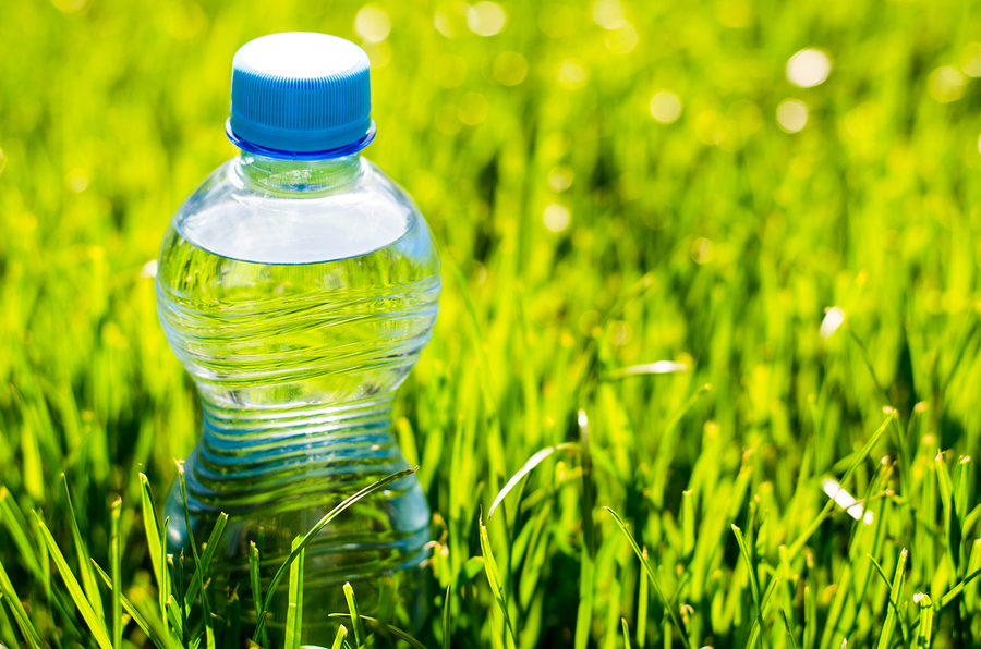 A clear bottle made of transparent thermoplastics on top of grass