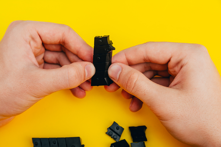 Hands holding a black prototype part for toy on a yellow background, inidcating a part make with rapid part prototyping