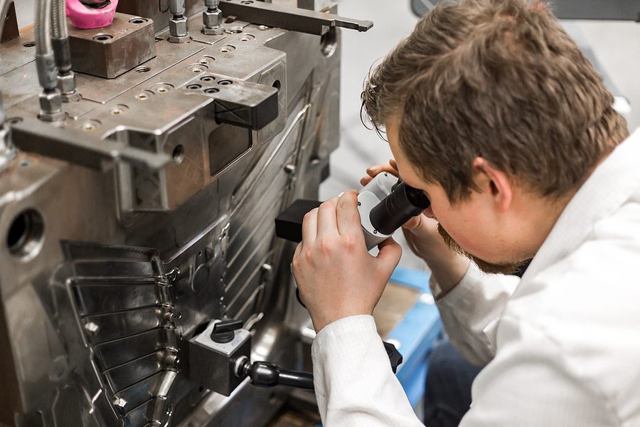 A quality control engineer looking for part deficiencies by using a microscope next to a injection molding machine