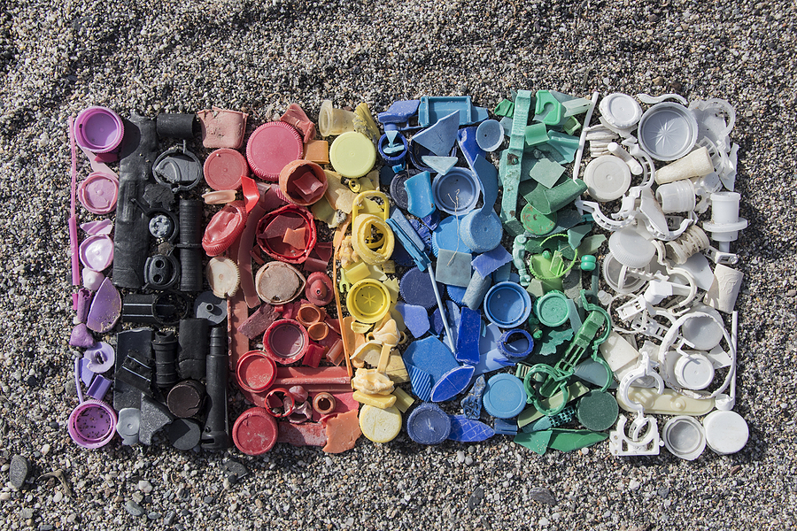 A gradient of different colored plastics arranged int he order of a rainbow on sand, used to signify discoloration in plastic injection molding.