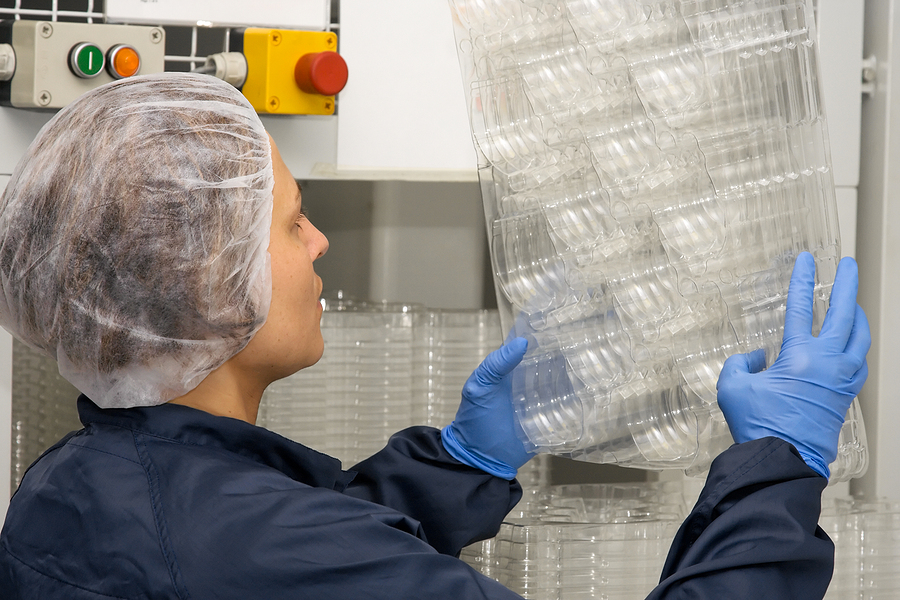 A female technician inspecting plastic packages generated by thermoforming
