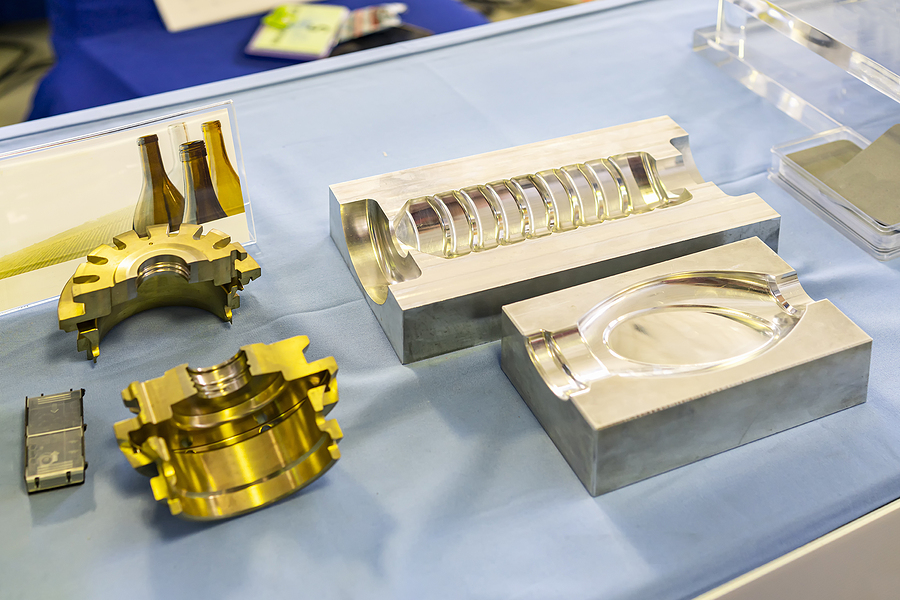 Two bottle-shaped plastic injection molds laying side by side meant to demonstrate prototype tooling in injection molding.