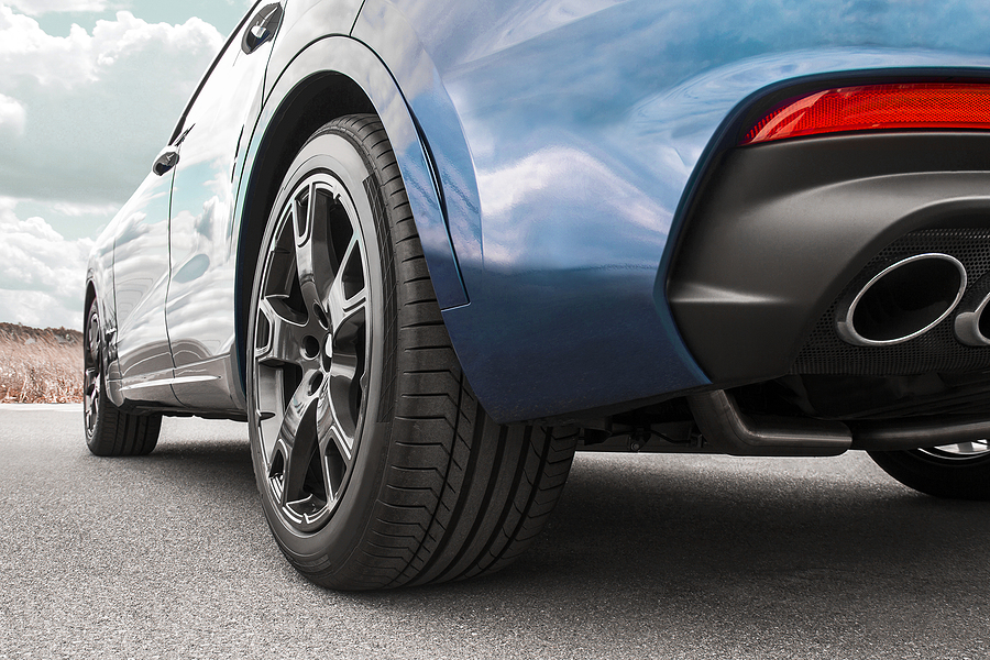 A close-up of the rear of a blue car depicting a plastic plate surrounding the exhaust pipe.