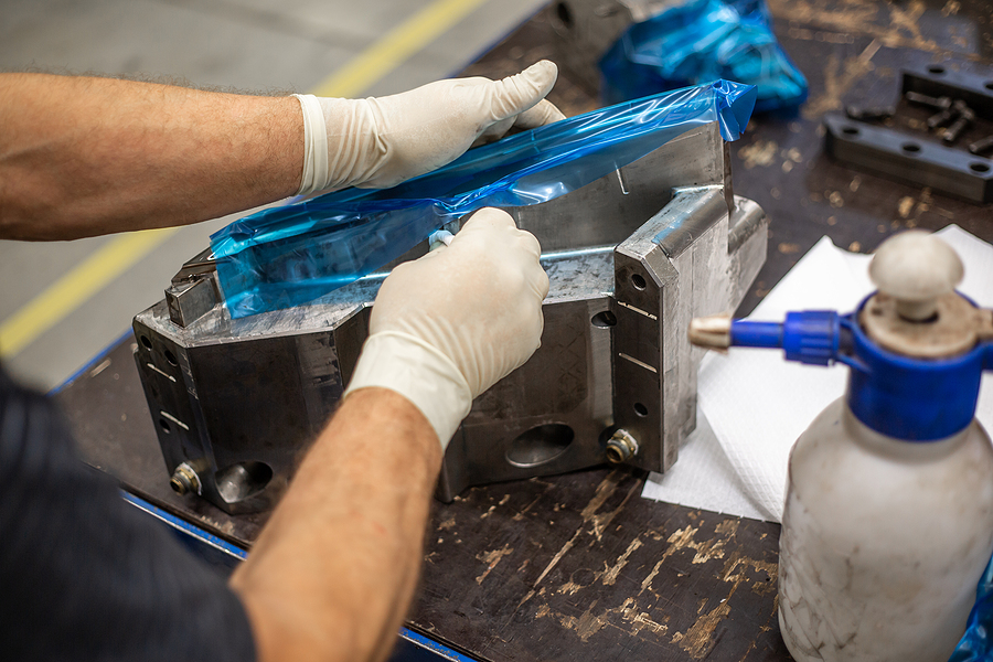 A plastic injection molder maintaining a large mold to indicate the advantages of sourcing your injection molding.
